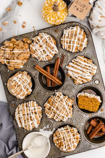 finished pumpkin spice muffins in a muffin tin with cinnamon sticks and frosting drizzled