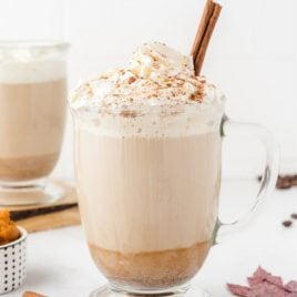 homemade pumpkin spice latte close up in a glass mug showing layers of the drink