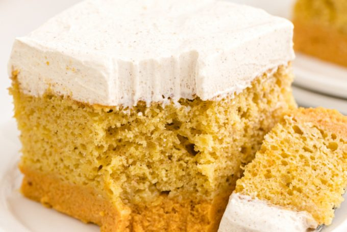 pumpkin magic cake showing three distinct layers on a white plate with a bite on a fork