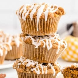 close up shot of Pumpkin Spice Muffins drizzled with icing stacked on top of each other