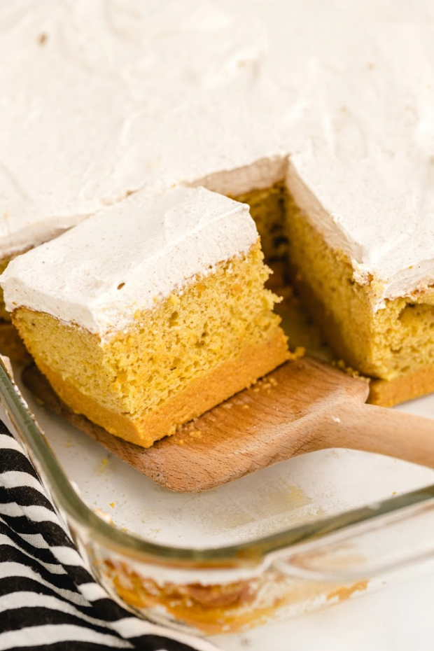 pumpkin magic cake in cake pan with a slice about to be removed and served