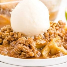 close up shot of a serving of apple crisp topped with a scoop of vanilla ice cream on a plate