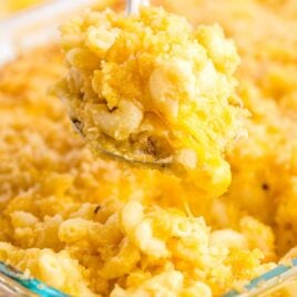 close up shot of Baked Mac and Cheese being grabbed from a baking dish with a large spoon