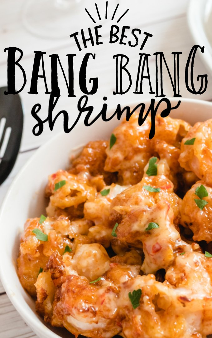 close up shot of bang bang shrimp with sauce poured on top in a white bowl