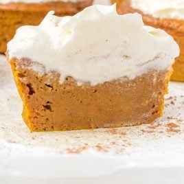 close up shot of impossible pumpkin pie cupcakes topped with whip cream