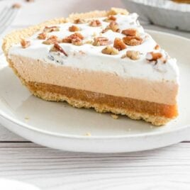 close up shot of a slice of Layered Pumpkin Spice Jello Pie topped with pecans on a plate
