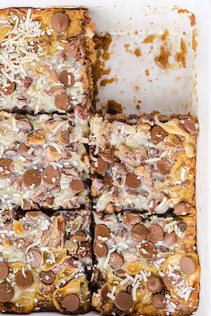 close up shot of magic cookie bars in a white baking pan