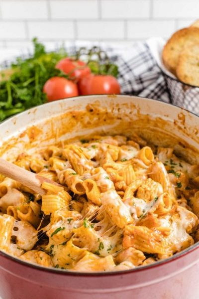one pot chicken parmesan pasta in a pot with a large wooden spoon