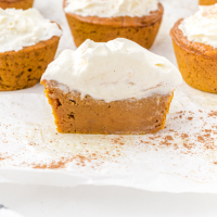close up shot of impossible pumpkin pie cupcakes with whipped cream on top