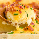 close up shot of mashed potato casserole in a clear pan being picked up with a wooden spoon