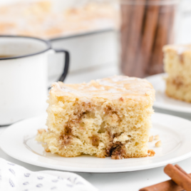 cinnamon roll cake on a white plate with a white coffee mug in the background