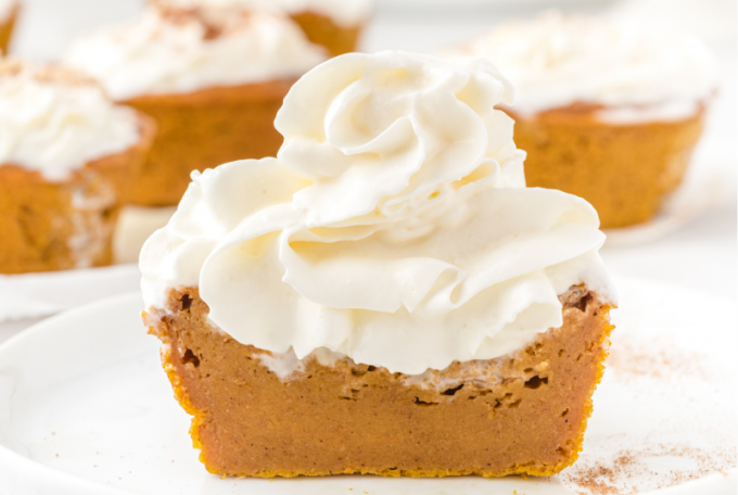 impossible pumpkin pie cupcakes with whip cream on the top on a white plate