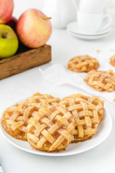 apple pie cookies piled on top of each other on a white plate