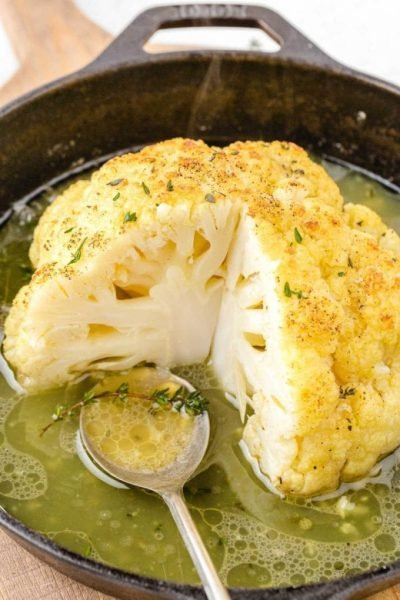 roasted cauliflower in a pot with broth and a spoon