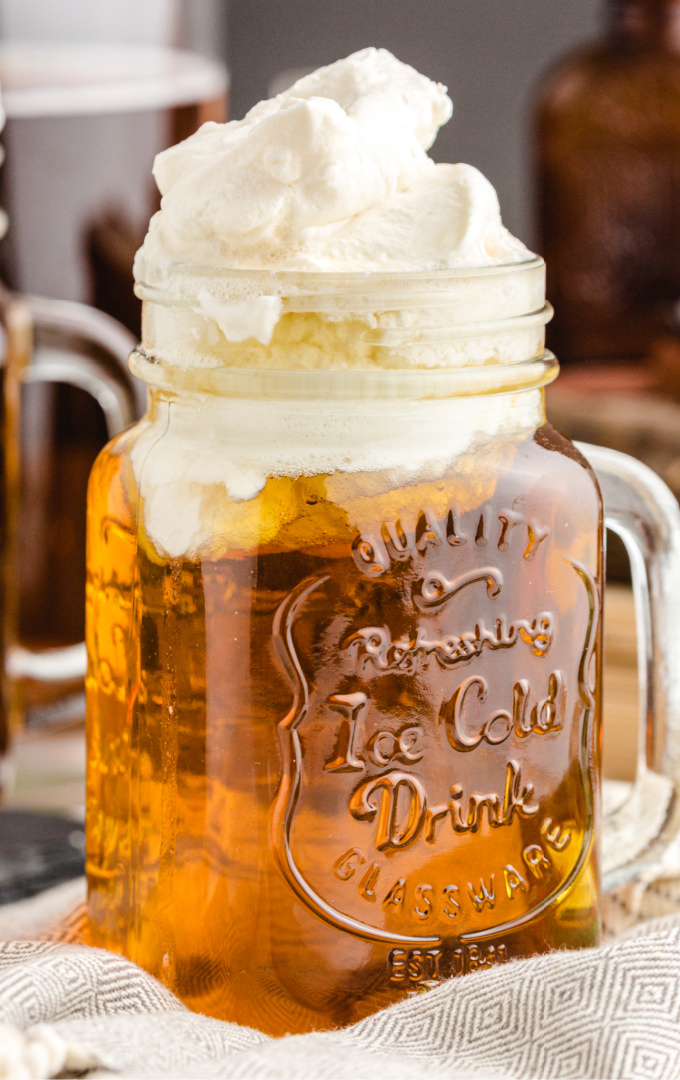 close up shot of butterbeer in a glass mug with whipping on top