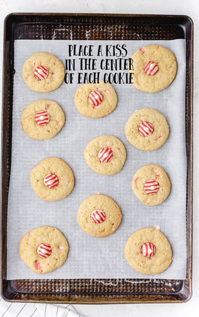 candy cane kiss cookies lined up on a baking pan