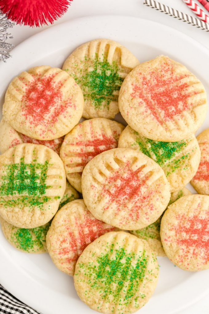 overhead shot of grandma's christmas sugar cookies piled on top of each other on a white plate