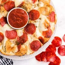 close up overhead shot of pull apart pizza bread with a cup of marinara sauce