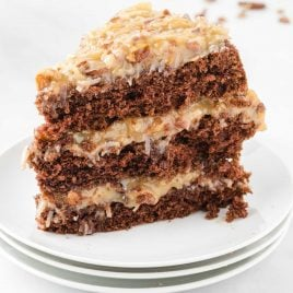 close up shot of a slice of German Chocolate Cake with coconut pecan frosting on a plate