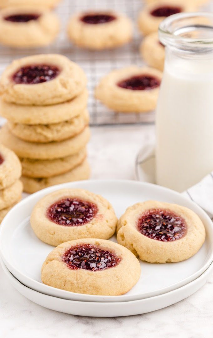 thumbprint cookies on a white plate with more cookies and a jug of milk in the back