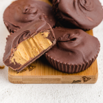 close up shot of homemade peanut butter cups stacked on a wooden board