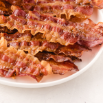 close up shot of oven baked bacon piled on top of each other on a white plate