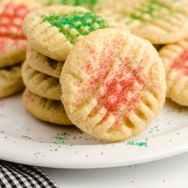 close up shot of grandma's christmas sugar cookies piled on top of each other on a white plate