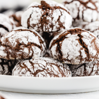 close up shot of chocolate crinkle cookies stacked on top of each other on a white tray