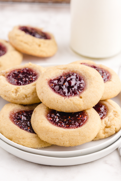 thumbprint cookies stacked on top of each other on a white plate with a jug of milk in the back