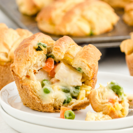 mini chicken pot pies showing its inside filling on a white plate