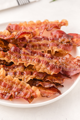 oven baked bacon piled on top of each other on a white plate