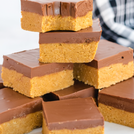 no bake peanut butter bars stacked on top of each other on a white plate