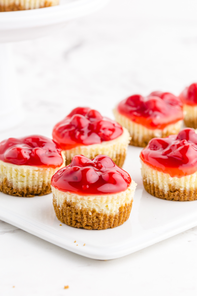 mini cherry cheesecakes lined up on a white plate