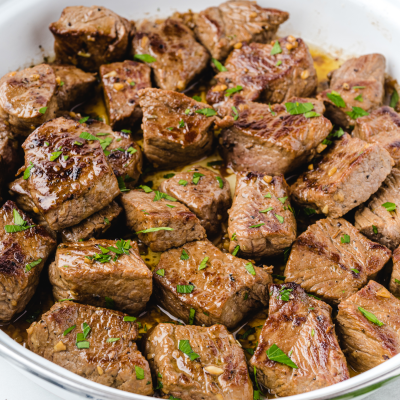 close up shot of steak bites in a white pan
