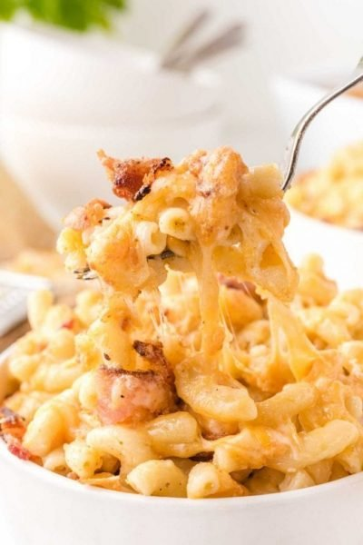 close up shot of bacon mac and cheese being picked up with a fork from a bowl