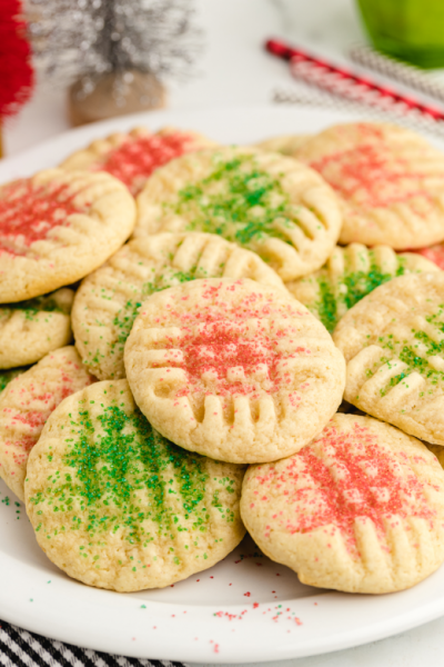 grandma's christmas sugar cookies piled on top of each other on a white plate