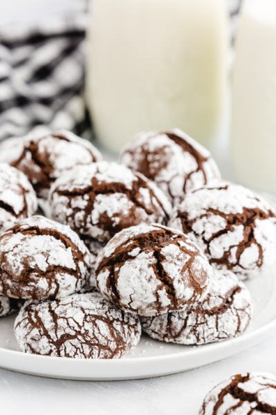 chocolate crinkle cookies stacked on top of each other on a white plate