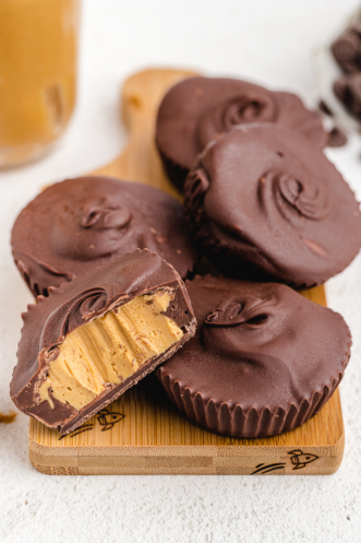 homemade peanut butter cups stacked on a wooden board