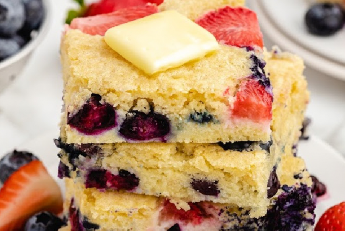 sheet pan pancakes stacked on top of each other on a white plate with fruits