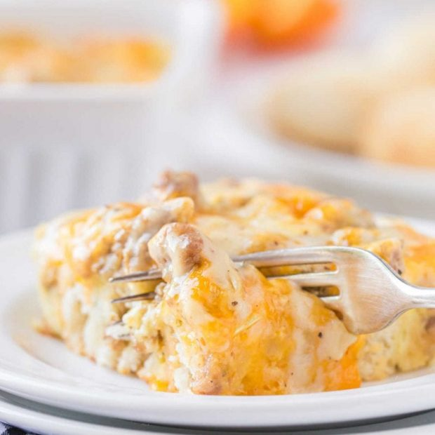 close up shot of a serving of Biscuits and Gravy Breakfast Casserole on a plate with a fork