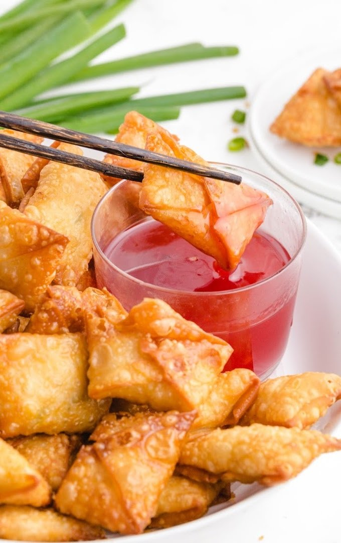 close up shot of crab rangoon being dipped in sauce with chop sticks on a white plate