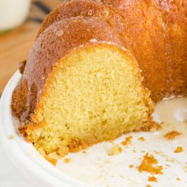 close up shot of kentucky butter cake with a slice missing on a white stand
