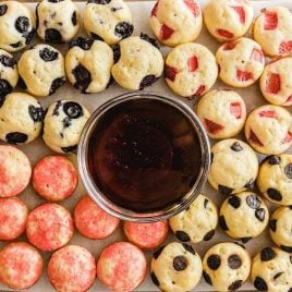 close up overhead shot of strawberry and blueberry Mini Pancakes on a serving tray with a bowl of syrup
