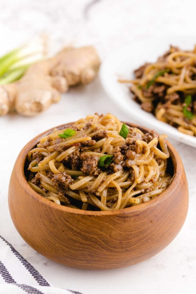 close up shot of Mongolian Beef and Noodle topped with green onions in a wooden bowl