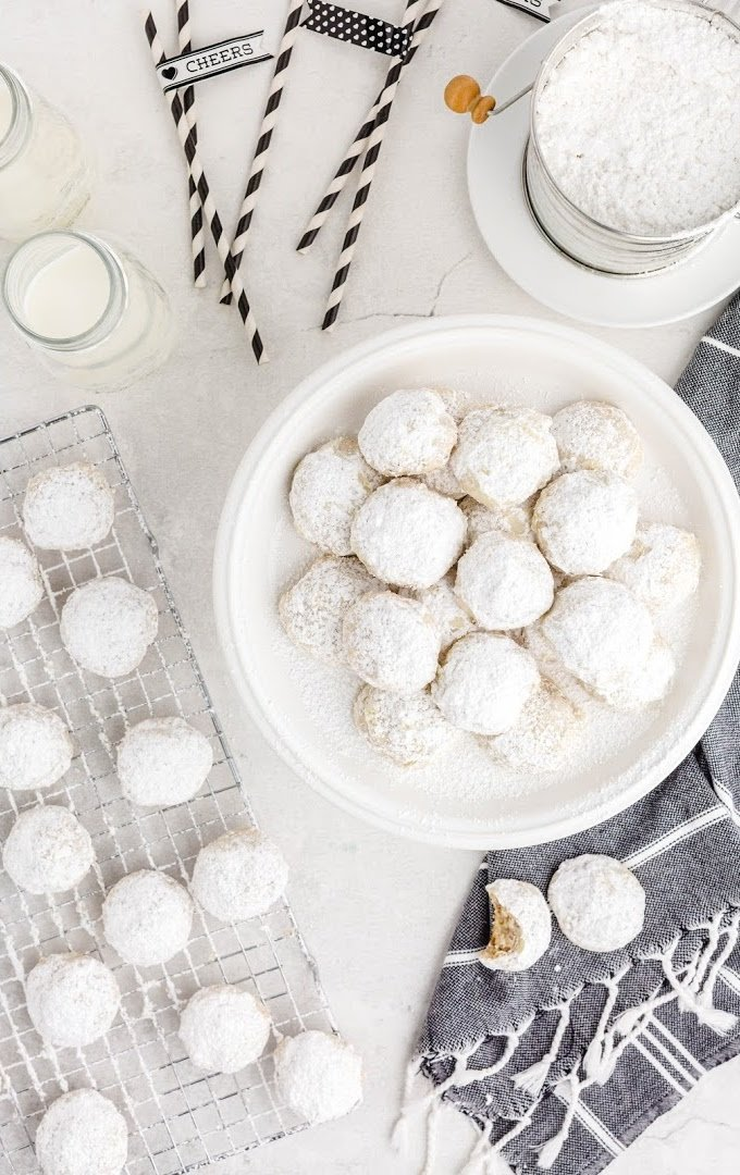 overhead shot of snowball cookies piled on top of each other and on a wire rack