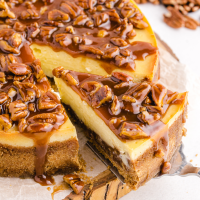 close up shot of pecan pie cheesecake with a slice being picked up