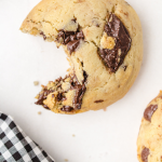 close up shot of cream cheese chocolate chip cookies with a piece bitten out of it