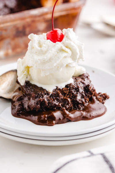 close up shot of hot fudge sundae cake with whip cream and a cherry on top on a white plate