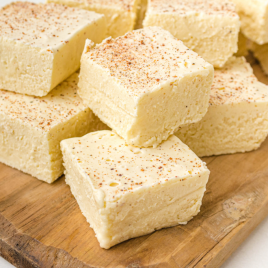 close up shot of eggnog fudge piled on top of each other on a wooden board