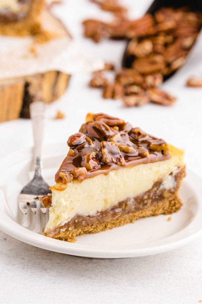 a slice of pecan pie cheesecake topped with caramel and pecans on a white plate